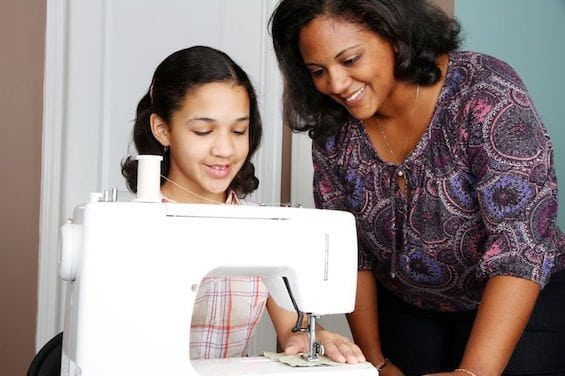 13291919 - girl and mother using a sewing machine to make crafts