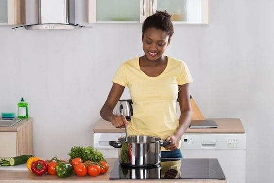 56063949 - young happy woman cooking meal on induction cooker in kitchen