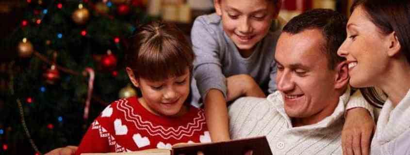 Modern family of four reading Christmas stories