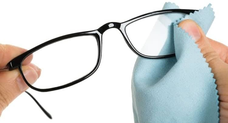 e5bedf998b close-up of person s hand cleaning eyeglasses with cloth