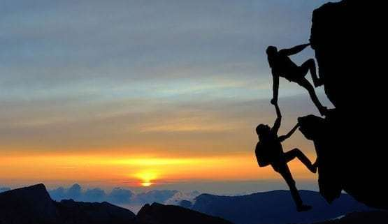 mountain-climber-helping-companion-reach-the-top