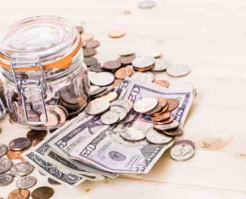 saving money into glass jar for future