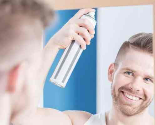 Young man is styling his hair using hairspray