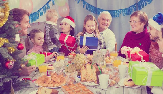 large family handing gifts to each other during a christmas dinner