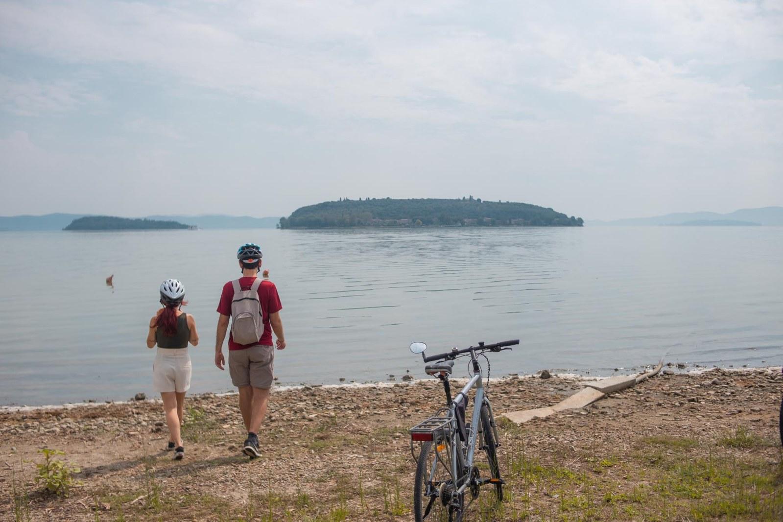 francesca e pietro camminano verso il lago trasimeno con la bicicletta a fianco