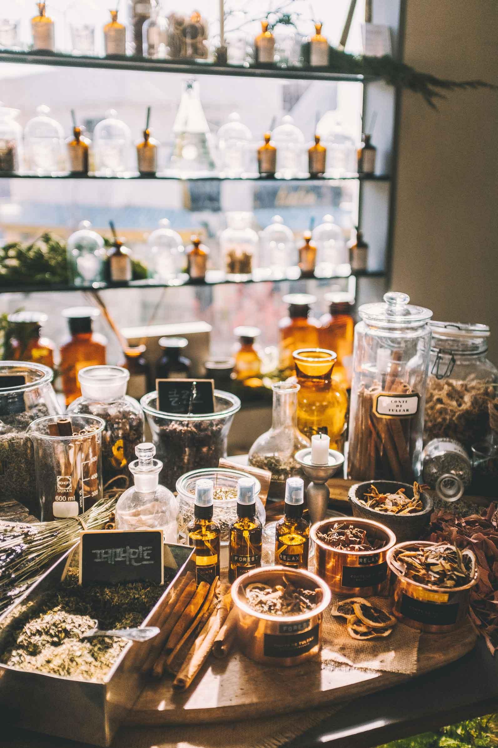 tavolo con gli ingredienti dei profumi e boccette di essenza profumate