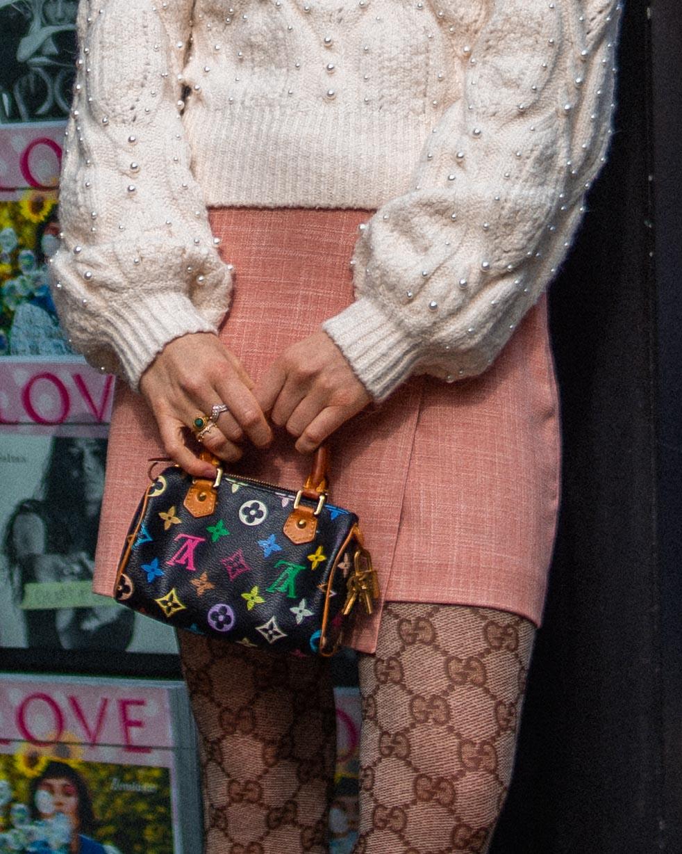 zoom su particolare con borsa mini di louis vuitton e calze gucci