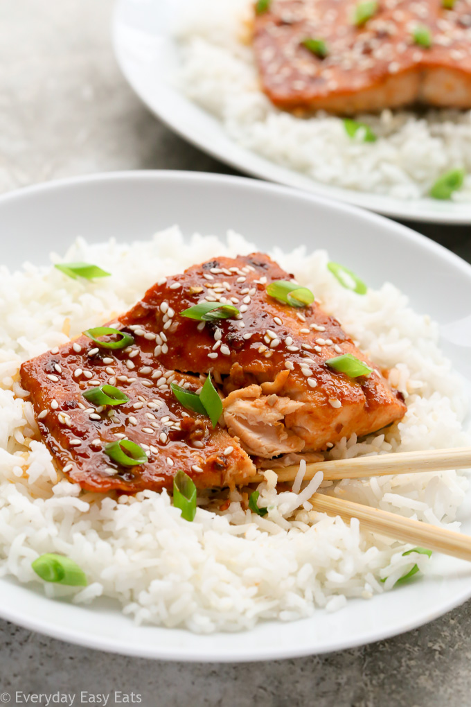 Close-up view of a plate of Asian Honey Sriracha Salmon on a bed of white rice with chopsticks.