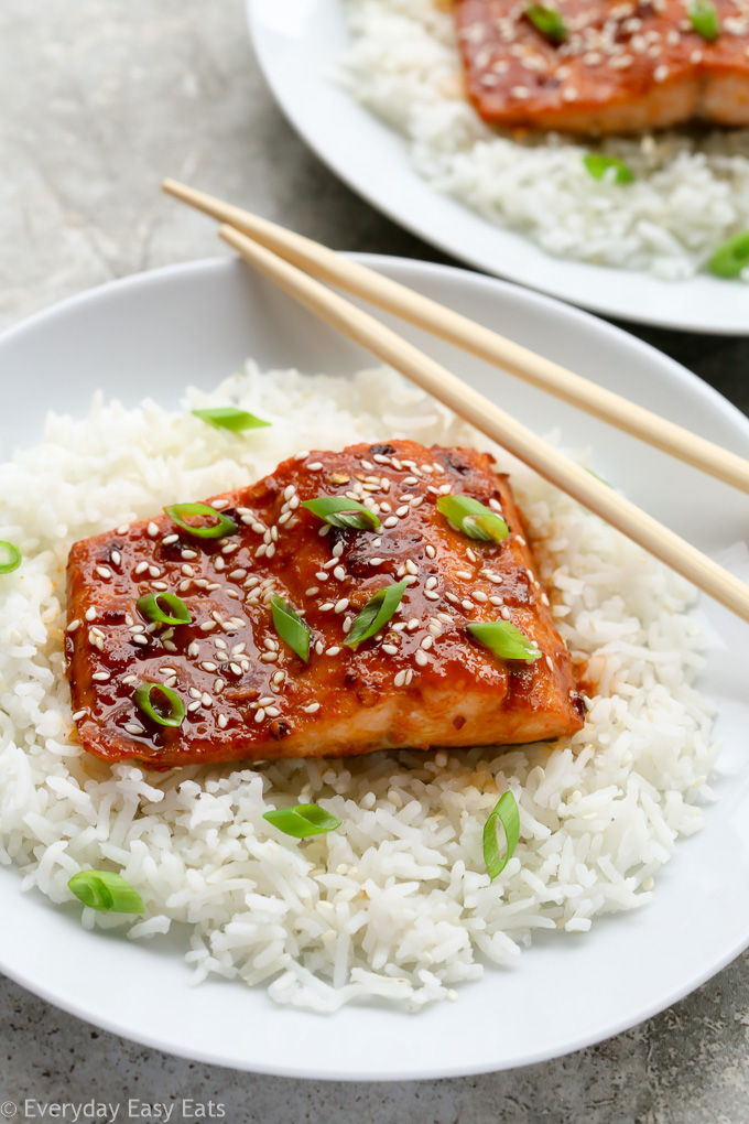 A plate of Asian Honey Sriracha Salmon sitting on a bed of white rice with chopsticks.