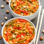Two bowls of Thai Curried Vegetable Rice with chopsticks and scattered peanuts and cilantro.
