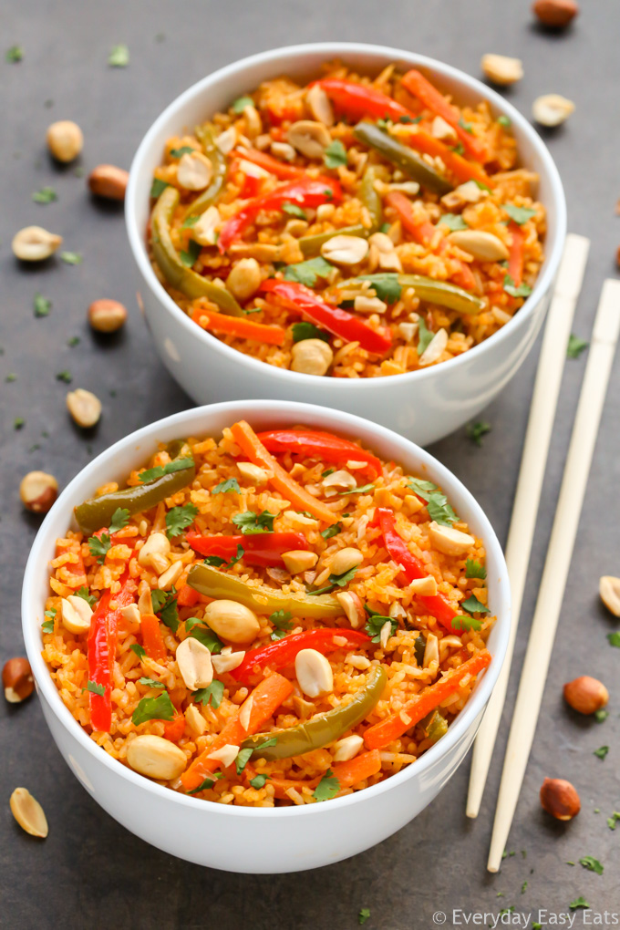 Two bowls of Thai Curried Vegetable Rice with chopsticks, scattered peanuts and cilantro.