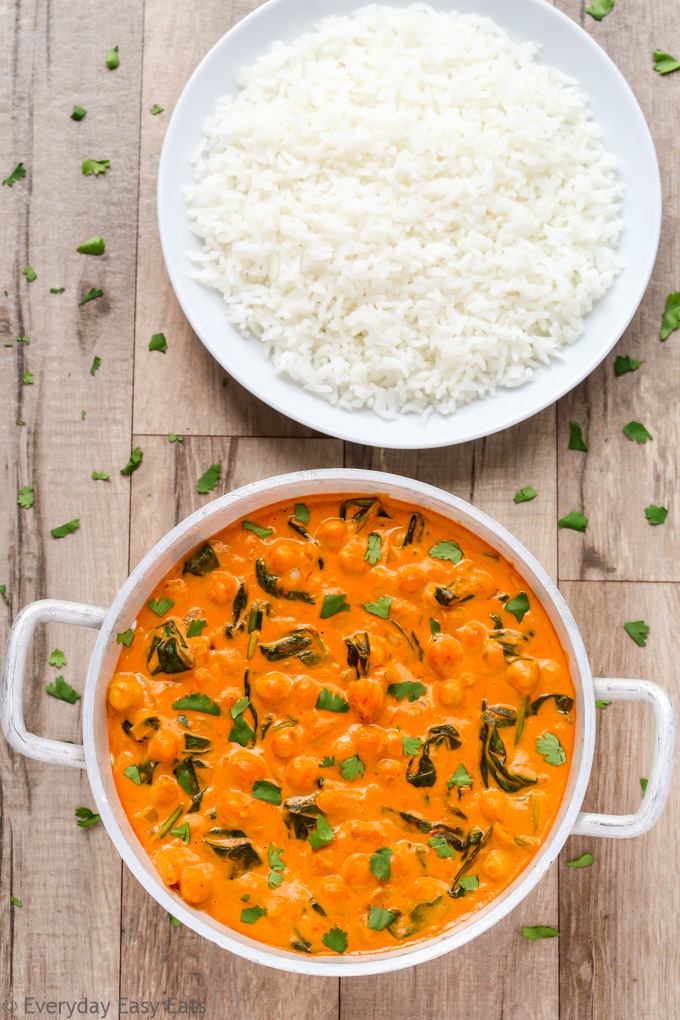 Overhead view of Indian Chickpea Coconut Curry in a silver serving bowl with a plate of white rice