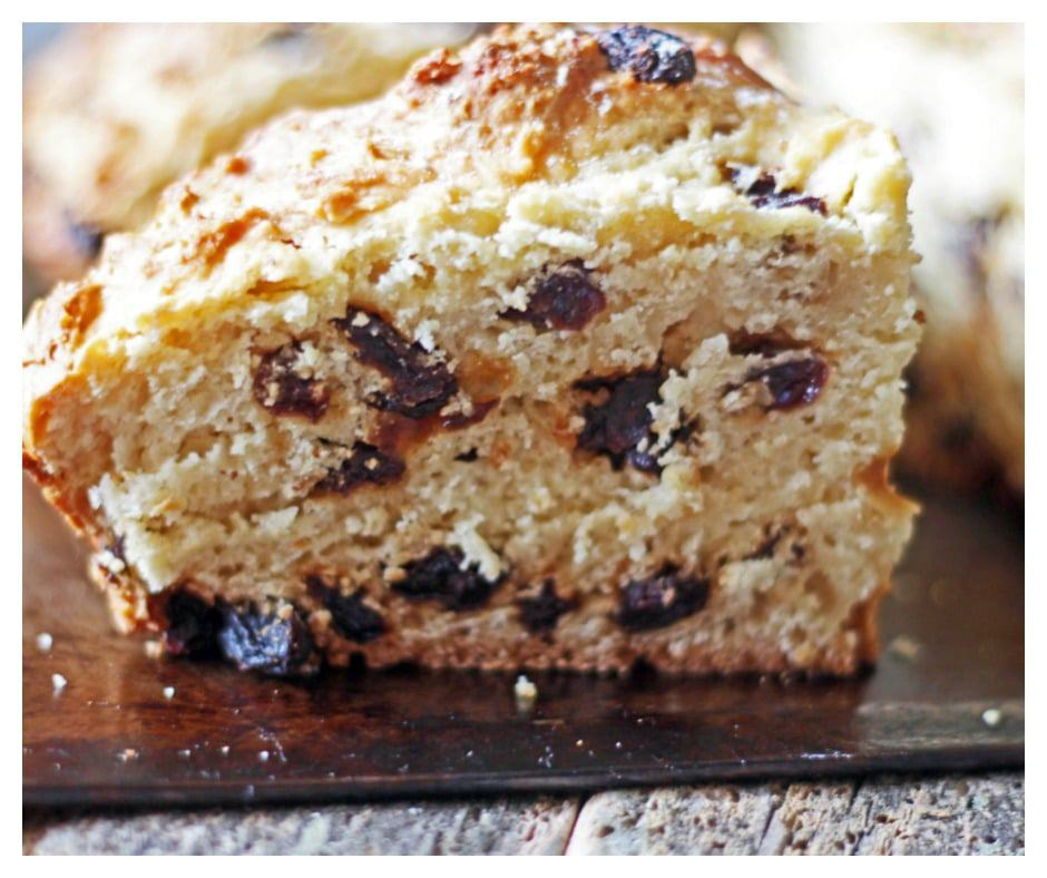 Tradition Irish Soda Bread with raisins is sliced on a baking tray