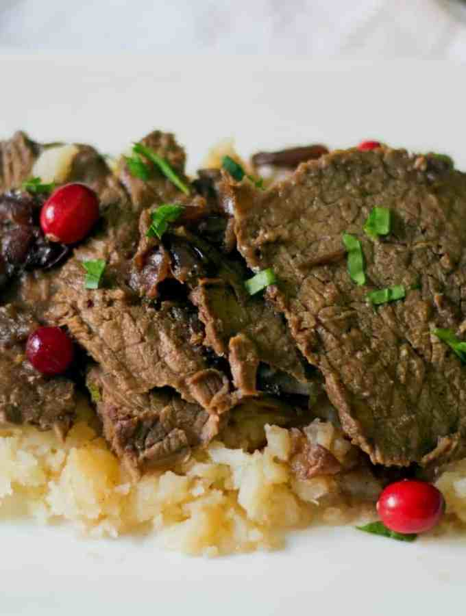 slow cooker cranberry pot roast on top of the best mashed potatoes They are drizzled with the pot roast gravy and chopped parsley