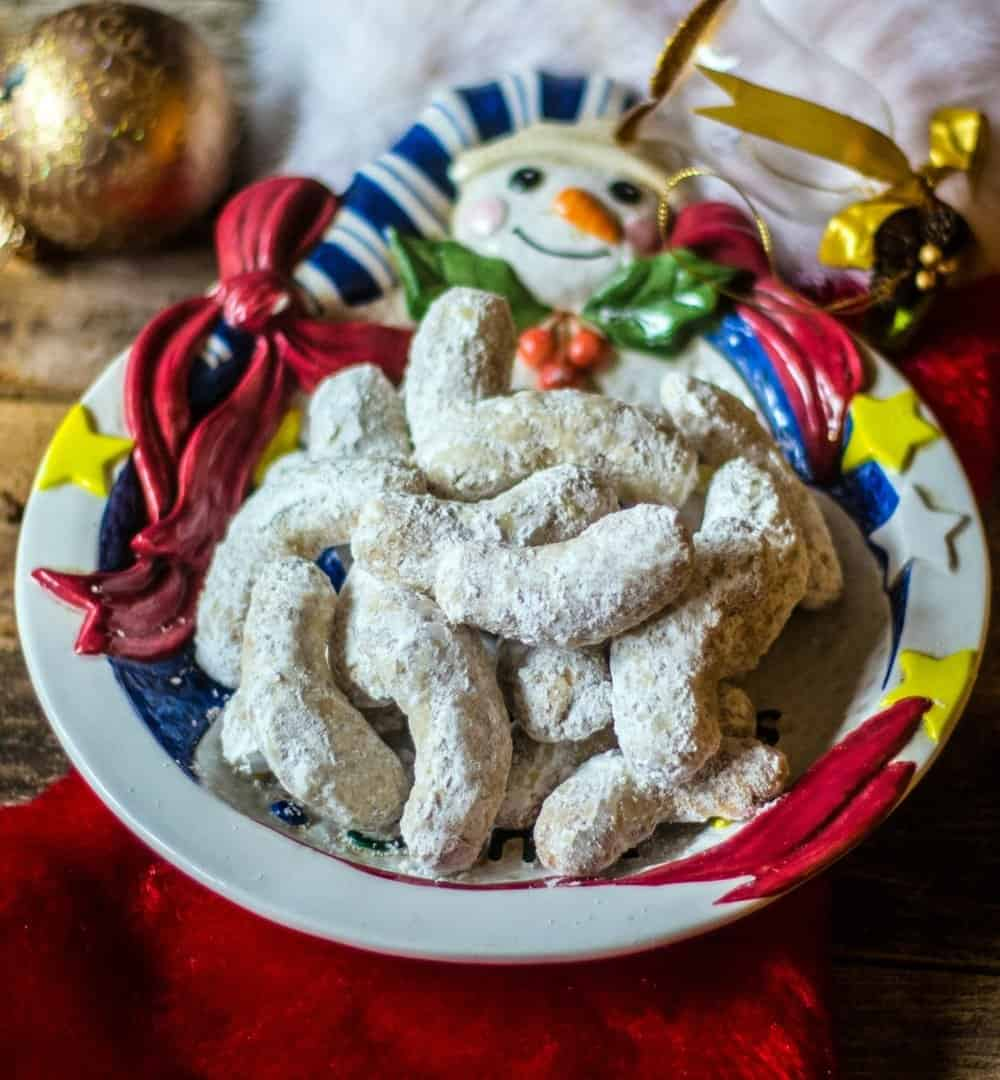 Festive pecan crescent cookies on a santa cookie platter.