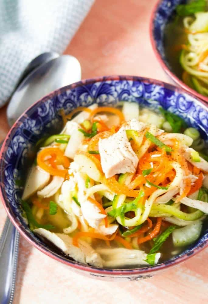 A side shot of zoodle chicken soup with zucchini zoodles,carrots, and shredded chicken in a decorative blue bowl with red trim
