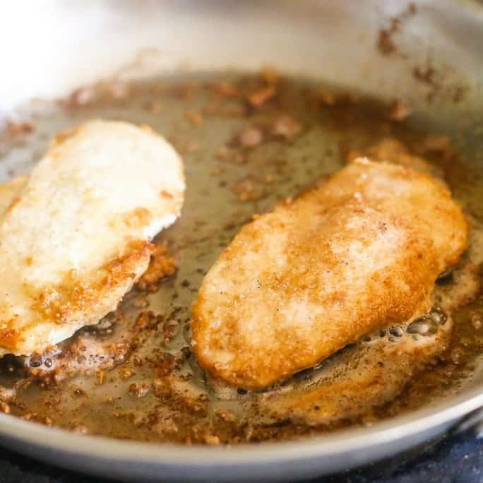 lemon chicken piccata with a golden crispy low-carb breading in a silver saute pan