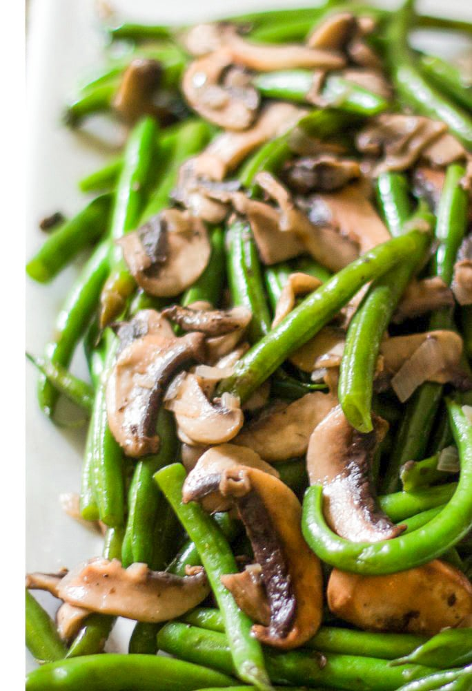 string beans with mushrooms. The string beans are blanched. Mushrooms and shallots are sauteed and this side dish is served on a white plate/
