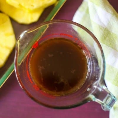 boozy rum sauce fora delicious grilled pineapple recipe in a measuring cup ready to cover fresh pineapple slices.