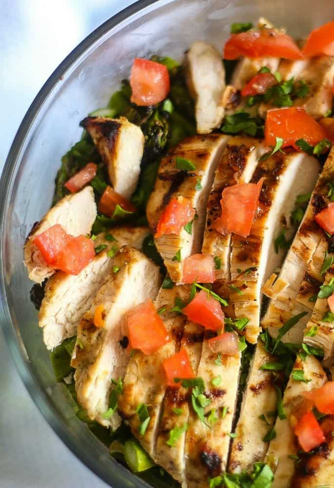 An aerial view of a tasty layered salad topped with grilled chicken with diced tomatoes and chopped parsley in a large glass bowl.