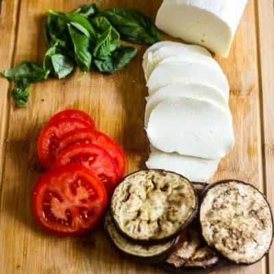 Sliced tomatoes, sliced fresh mozzarella, fresh basil, and grilled eggplant on a brown cutting board ready to make delicious grilled eggplant Caprese salad.