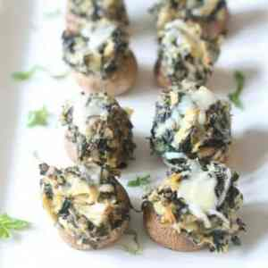 Tasty roasted spinach artichoke stuffed mushrooms with melted cheese on a white platter ready to be served.