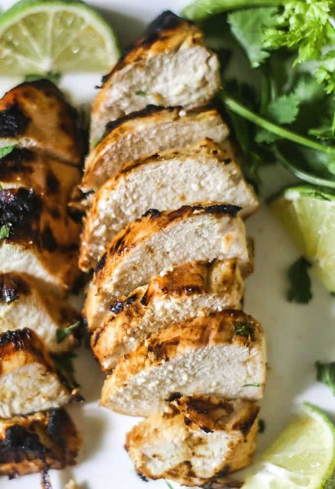 Grilled Dijon Lime Chicken on a white platter with cilantro and limes around the sliced chicken.