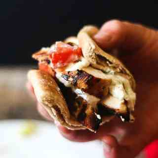 Grilled greek chicken gyros in a pita topped with cucumber, tzatziki and tomatoes.