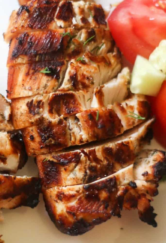 Grilled chicken sliced with cucumbers and tomatoes to make a tasty chicken gyro pita sandwich