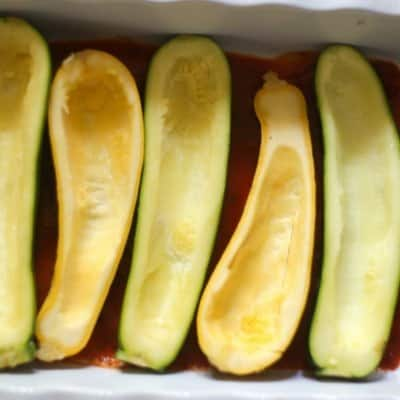 zucchini has been culled and in marinara sauce in a large casserole dish waiting for the additions of veggies, cheese, marinara, and fresh mozzarella