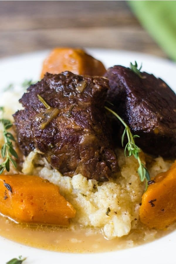 Beer Braised Short Ribs made in the Instant Pot topping mashed cauliflower and carrots.