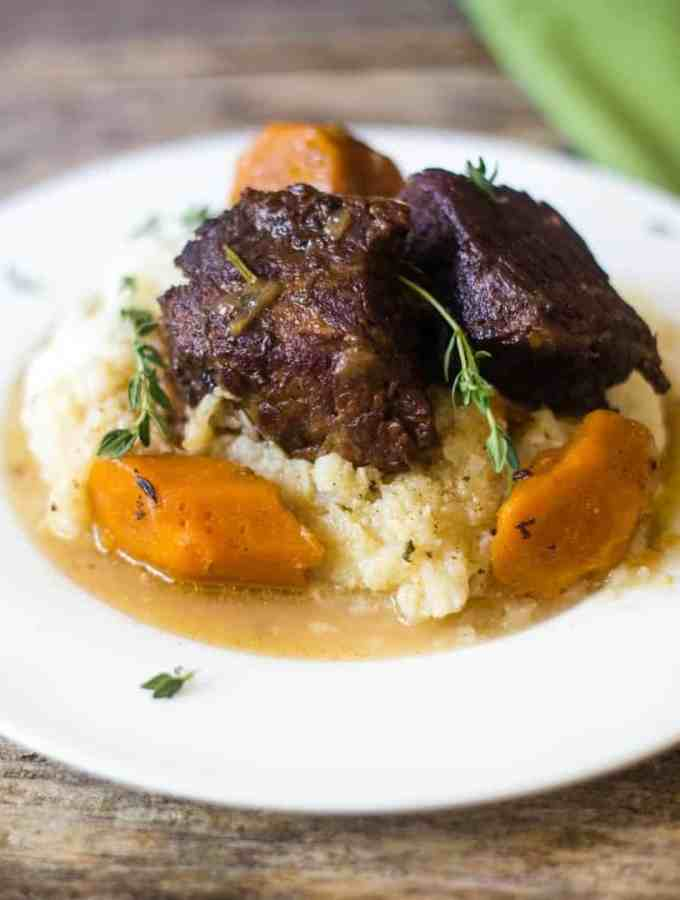 Delicious beer braised beef short ribs with carrots over mashed cauliflower