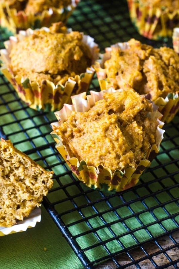Healthy pumpkin muffins in fall leaf muffin cups that have been baked and are cooling on a wire rack