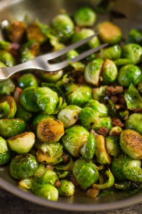 Tasty sauteed Brussels Sprouts with Prosciutto in a large saute pan after being cooked with white wine.