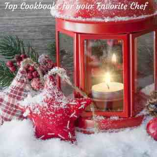 A festive Christmas scene with snow on the ground, a lanternand ornaments for gifts for top 10 cookbooks