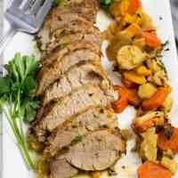 Sliced pork tenderloin with root veggies on a white platter