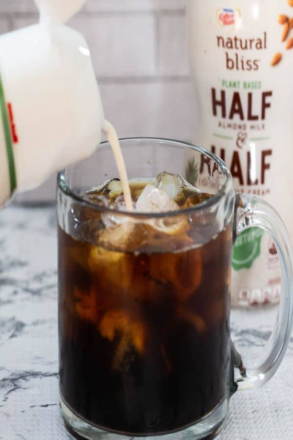 Iced coffee in a glass mug with natural bliss plant based half and half being poured in the glass