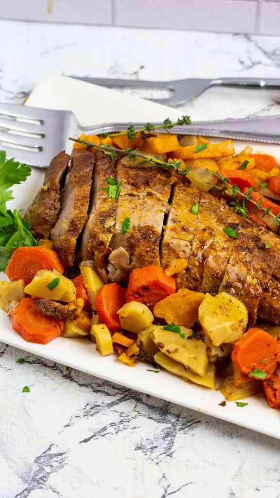 pork tenderloin with root veggies on a white platter