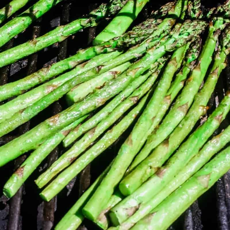 Asparagus stalks seasoned with olive oil and simple seasoning on the grill.