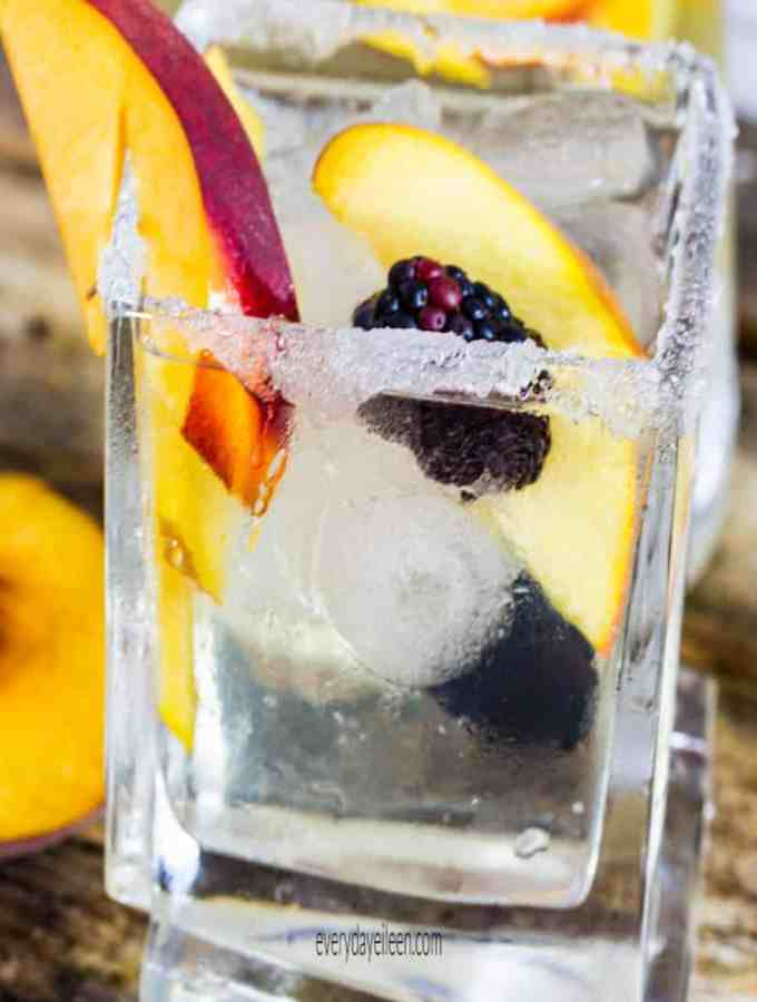 Peach sangria in a square glass filled with ice and peach slices and a sugar rim on the glass.