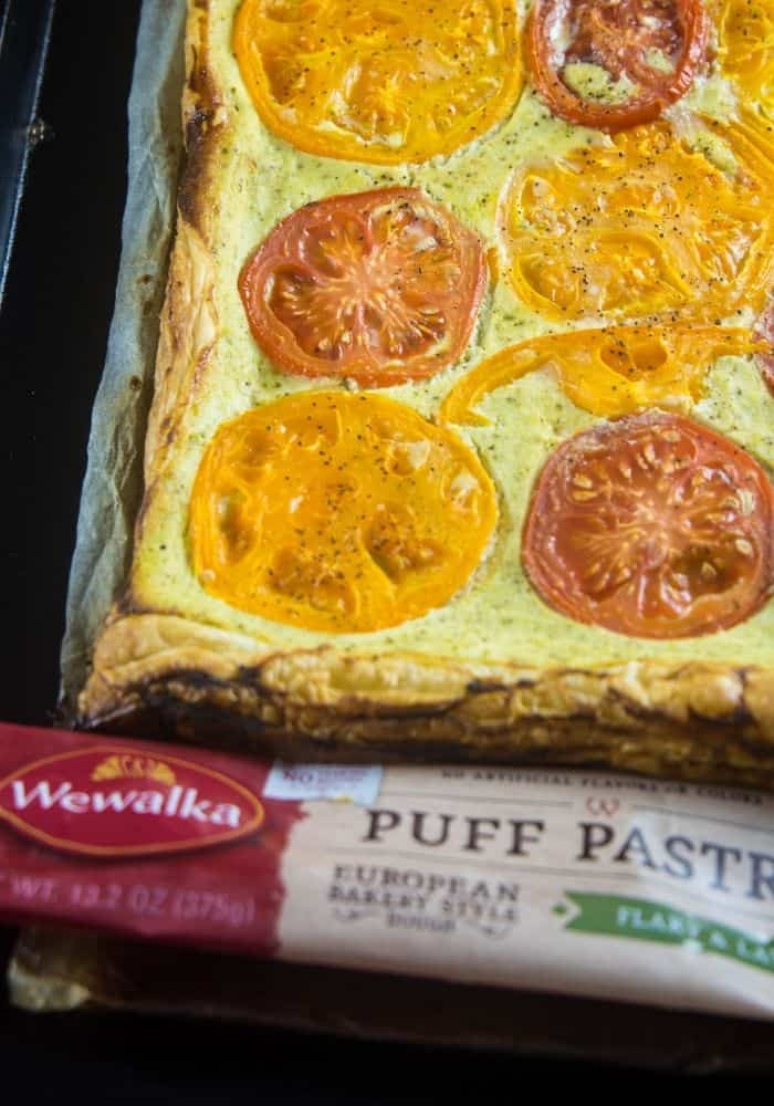 Ricotta tomato tart on a large baking sheet with the Wewalka puff pastry wrapper at the base of the pan.