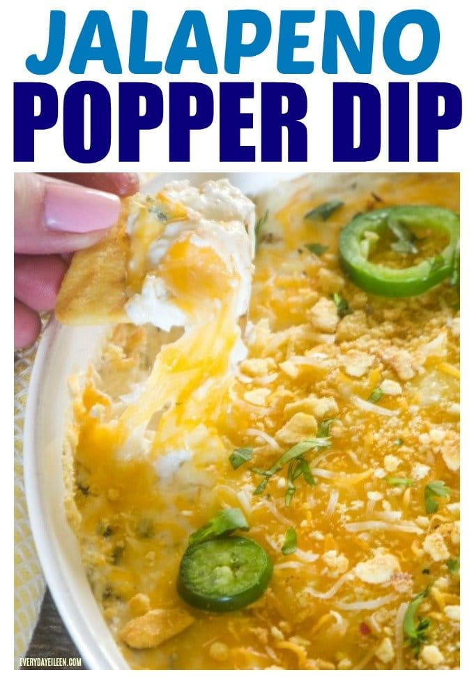 Jalapeno popper dip in a white dip bowl and a chip is being pulled up with melted cheese and popper dip