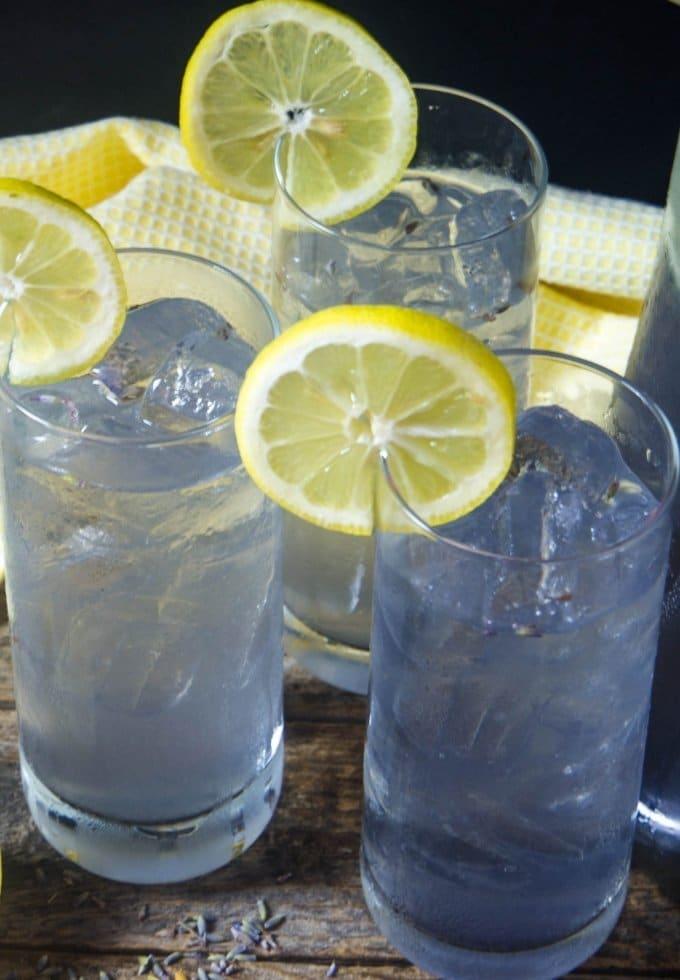 lavender lemonade in joy jolt glasses topped with fresh lemon wedges