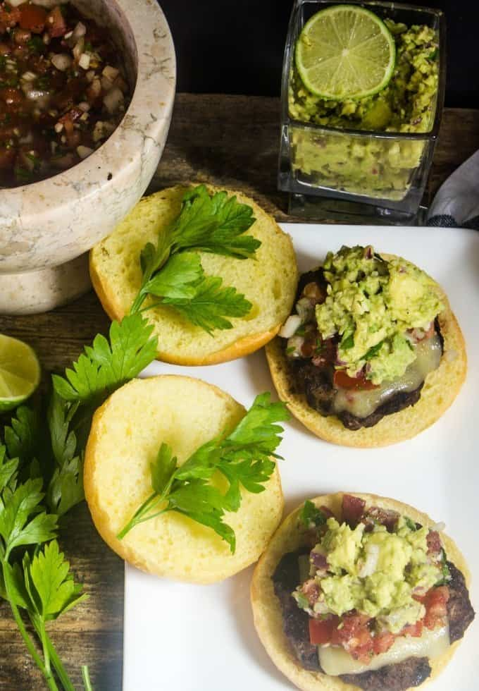Delicious taco burgers topped with pico and guacamole with fresh cilantro leaves on the plate.