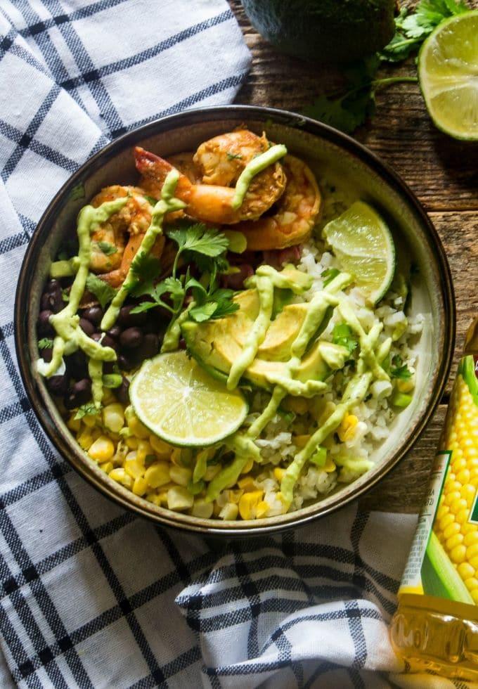 Delicious shrimp taco bowl on a plaid cloth topped with avocado yogurt dressing