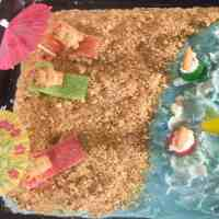 Festive beach cake decorated with blue frosting and graham cracker sand with teddy graham bears on the beach under beach umbrellas