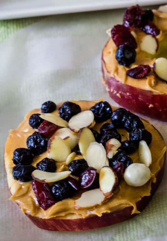 Apple slice topped with peanut butter and dried fruit.