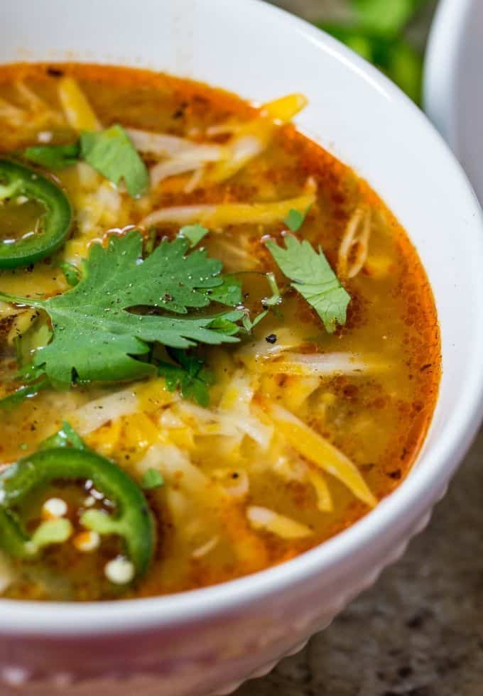 slow cooker chicken enchilada soup topped with fresh cilantro, fresh jalapeno slices and shredded cheese.