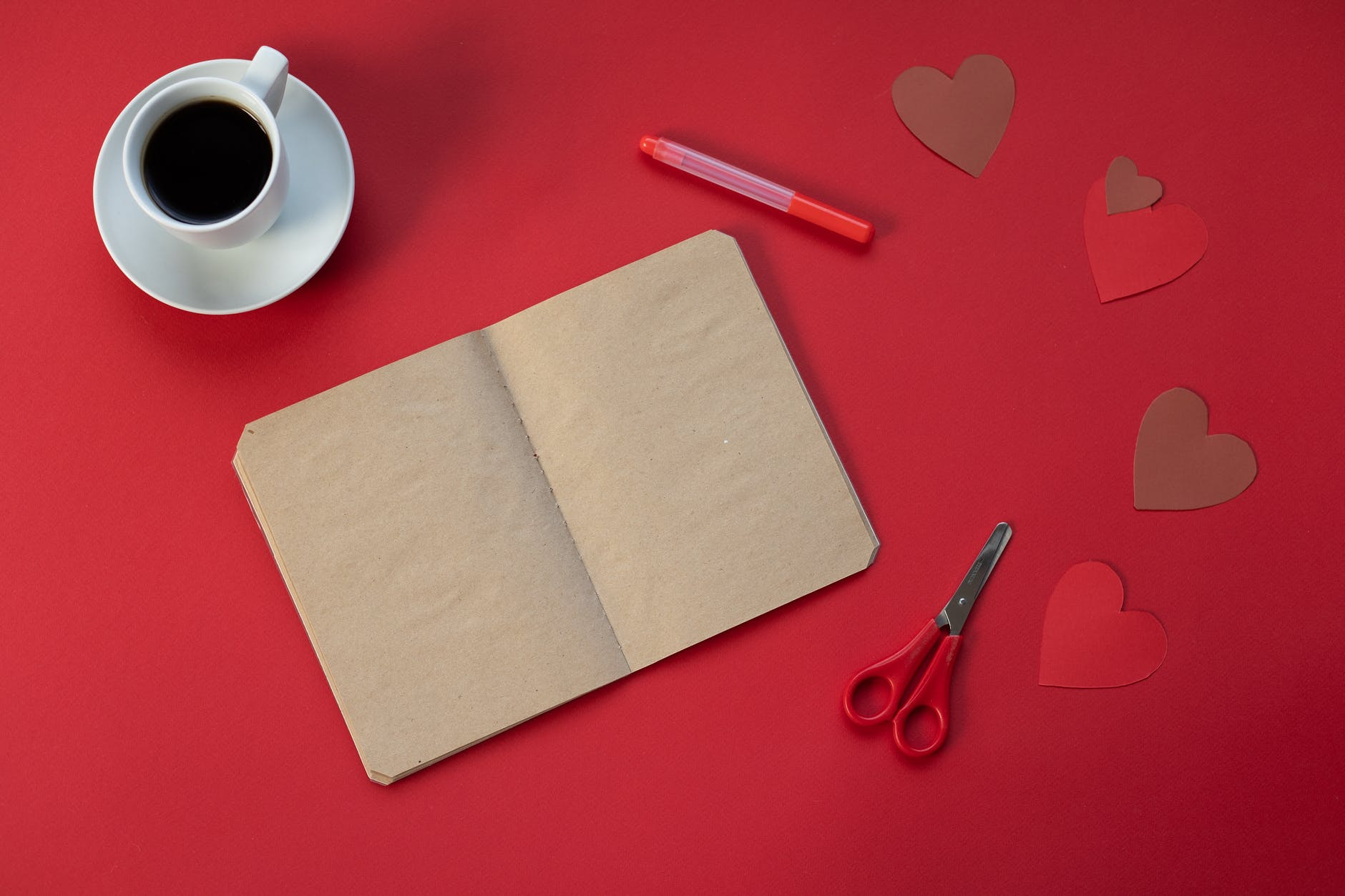 empty notepad near coffee and paper hearts