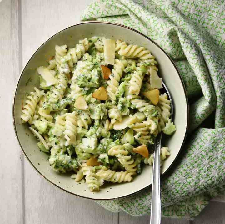 Top down view of pasta with broccoli and spoon in light green coloured bowl wrapped in green cloth.